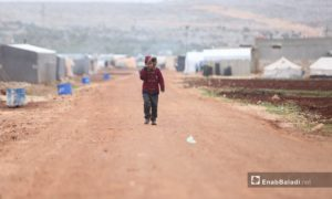 A child walking against the wind in al-Dana displacement camps - 15 December 2020 (Enab Baladi-Youssef Gharibi)