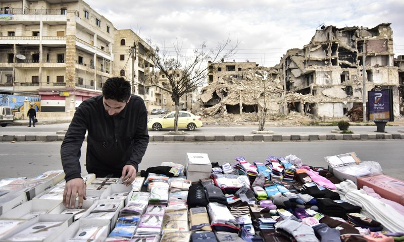 A Socks selling stall in front of a destroyed building in the Saif al-Dawla neighborhood in Aleppo city - March 2020 (Sputnik agency)
