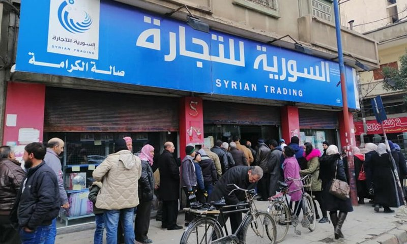 Syrian people wait in a queue to get food items in front of one of the branches of the Syrian Trade Establishment (Internet)
