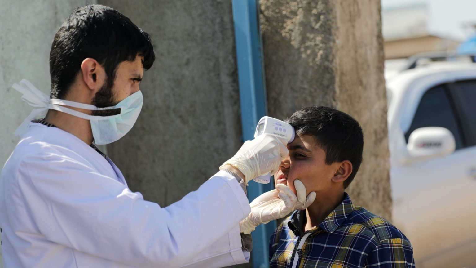 Paramedic taking a child's temperature within COVID-19 preventive measures in Azaz city, northern countryside of Aleppo —11 March 2020 (Reuters)