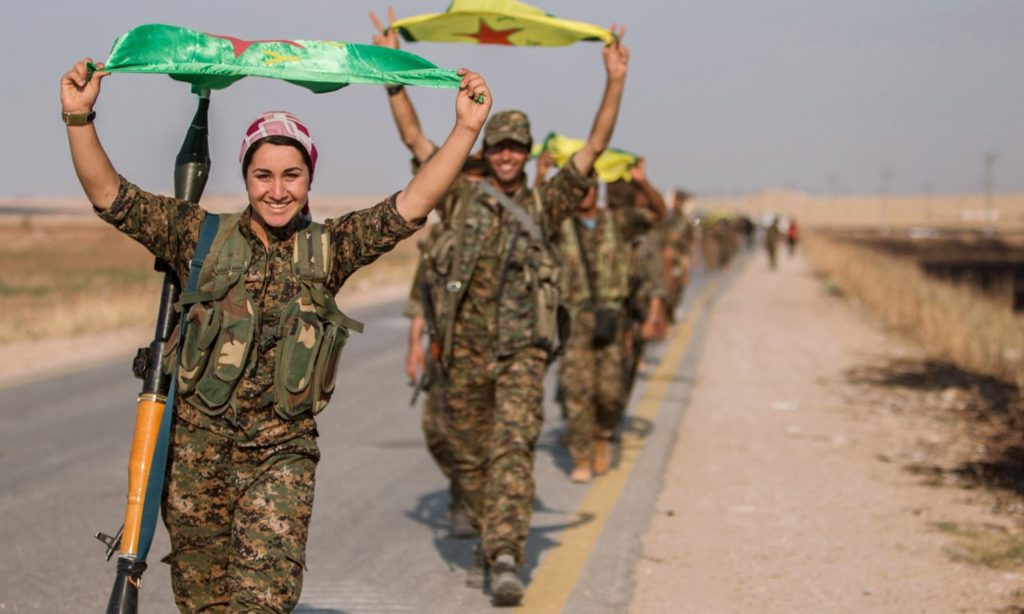 Kurdish fighters waving YPG flags while making victory signs - 2017 (Reuters)