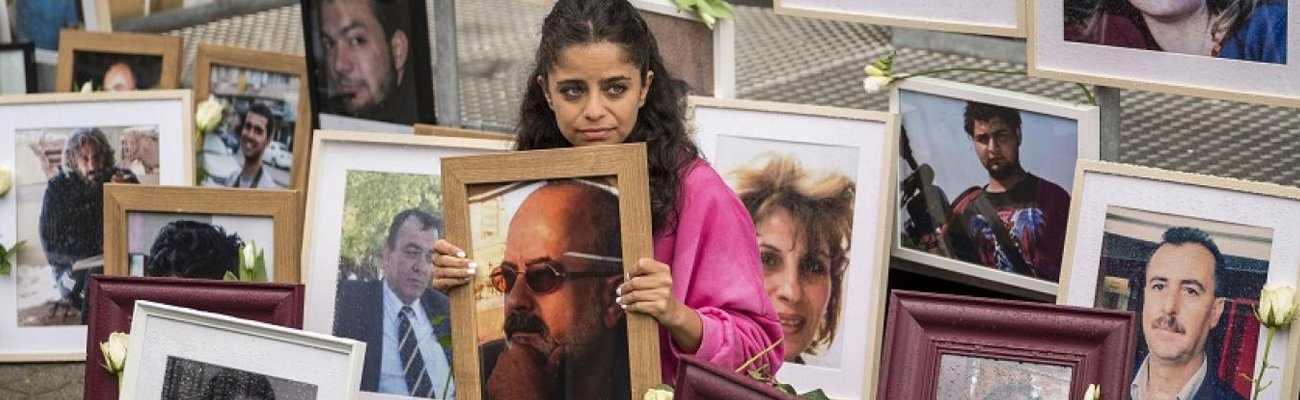 Wafa Mustafa sits between pictures of victims of the Syrian regime as she holds a picture of her father, outside the Koblenz Court building, west of Germany— 4 June 2020 (AFP/Thomas Lohnes)