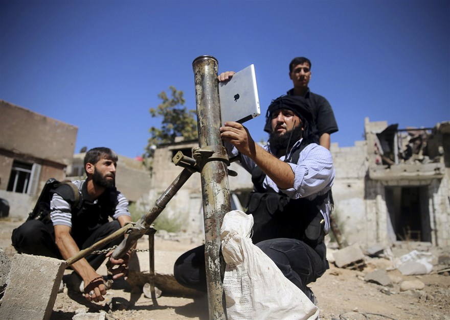A fighter of the Ansar Dimashq brigade of the Free Syrian Army using an iPad to launch a home-made mortar shell in Jubar neighborhood, Damascus—15 September 2013 (Reuters)
