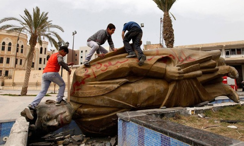 Children playing on the downed statue of Hafez al-Assad, the former president and father of the current head of the Syrian regime, Bashar al-Assad, al-Raqqa governorate in eastern Syria - 13 March 2013 (Reuters)