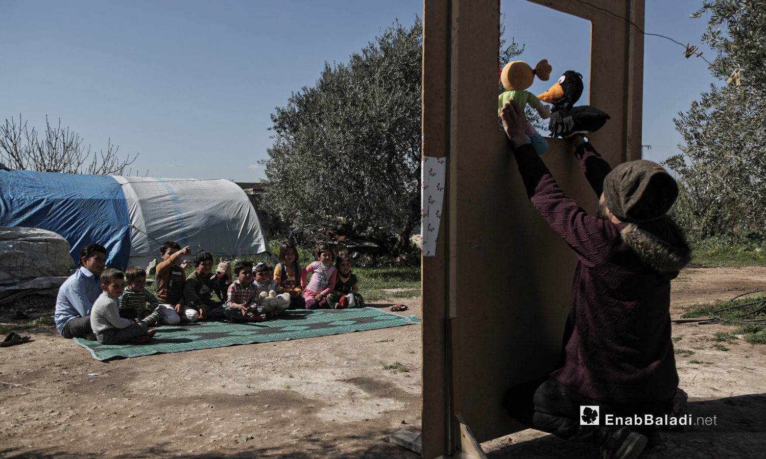 Displaced children watching a puppet show staged by al-Harah theater group in one of the displacement camps near Idlib city - 28 March 2021 (Enab Baladi / Yousef Ghuraibi)