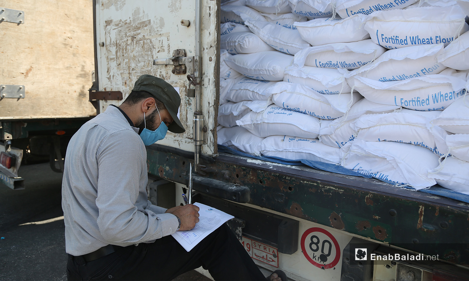 Employee at Bab al-Hawa Border Crossing between Syria and Turkey counting aid items delivered to Syria —18 September 2020 (Enab Baladi / Youssef Ghuraibi)