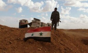 A soldier from the Syrian regime forces standing near the regime's flag - (NGUOIDUATIN)
