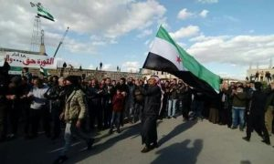 A protester in Daraa raising the flag of the Syrian revolution - 18 March 2021 (Facebook)