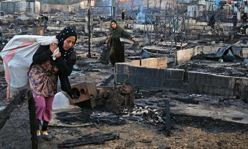 Two Syrian refugee women walking through the remains of a burnt camp in northern Lebanon (AFP)