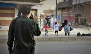 "A fighter from the Kurdish Internal Security Forces (ISF) or ""Asayesh"" on alert while civilians are fleeing their neighborhoods in al-Qamishli city following clashes with the pro-government National Defense Forces (NDF) - Asayesh"