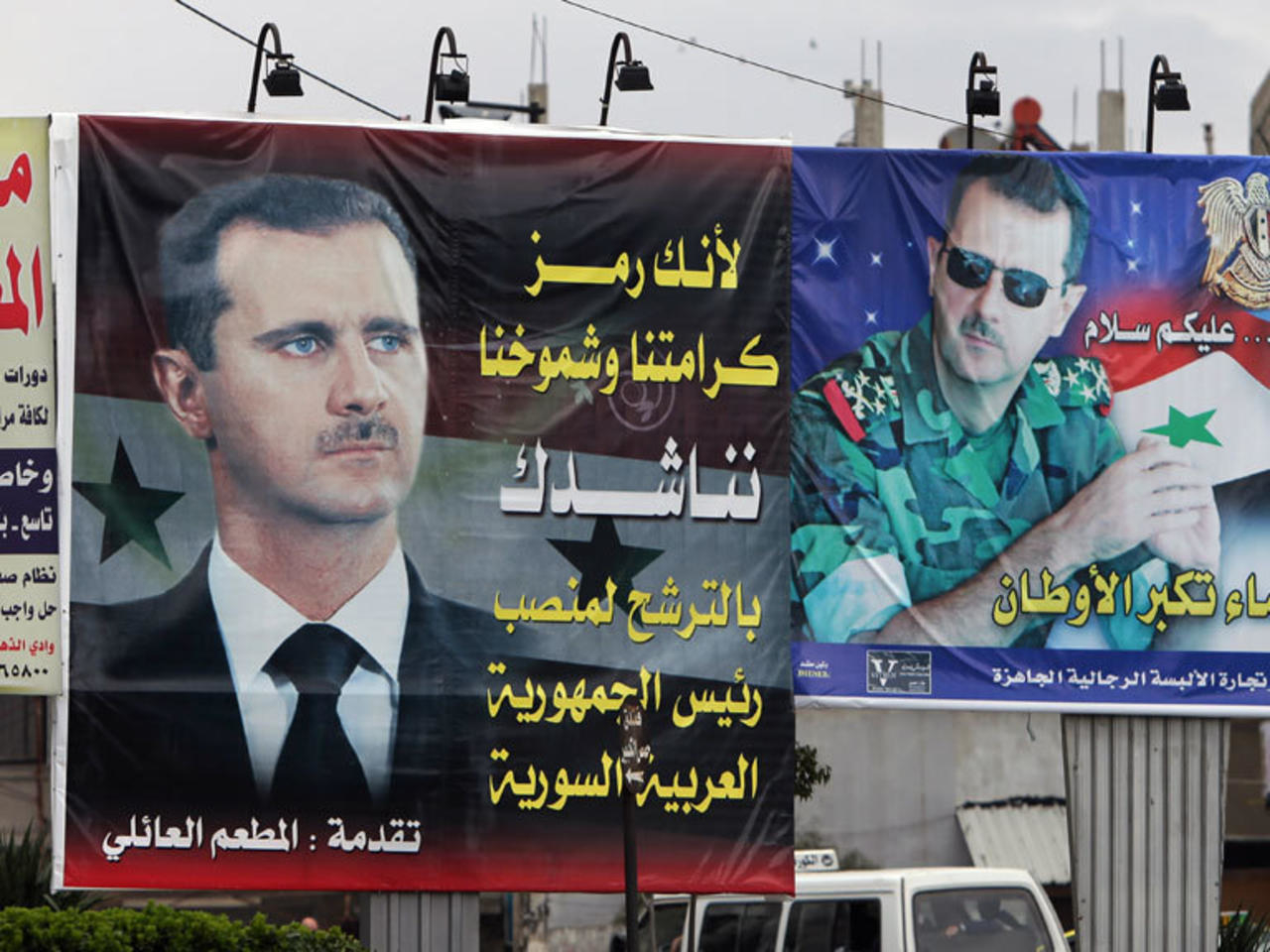 Poster-size photograph of the head of the Syrian regime Bashar al-Assad, with an inscription expressing support for his decision to run for the Syrian presidential elections—2014 (AFP)