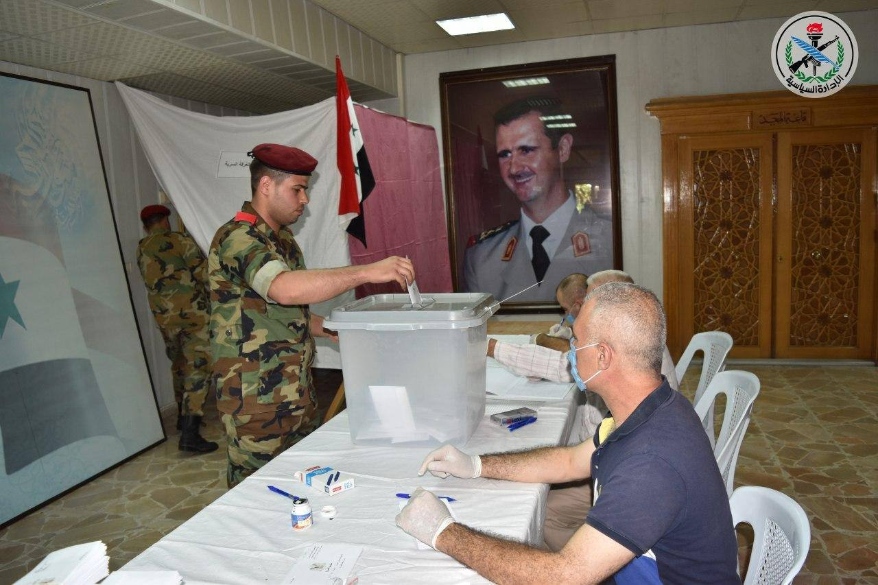 A Syrian soldier casting his vote at a polling station during the People's Council elections, with a picture of the president of the Syrian regime, Bashar Al-Assad, appearing in the background – 19 July 2020 (SANA)