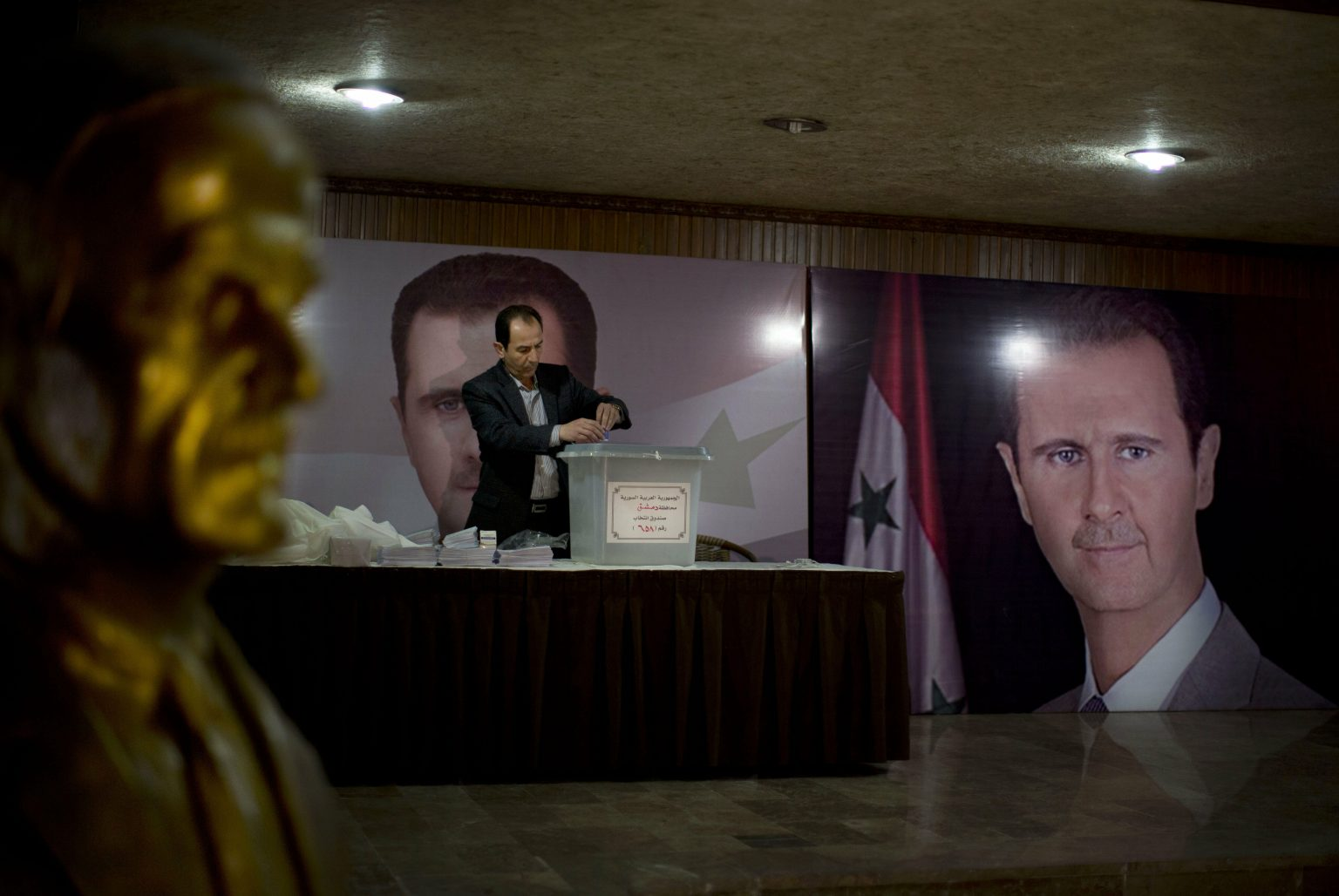 A Syrian poll worker waiting for voters at a polling station for the People's Council elections, where posters of the head of the Syrian regime, Bashar al-Assad, are displayed, along with a statue of al-Assad the father - April 2016 (AP)