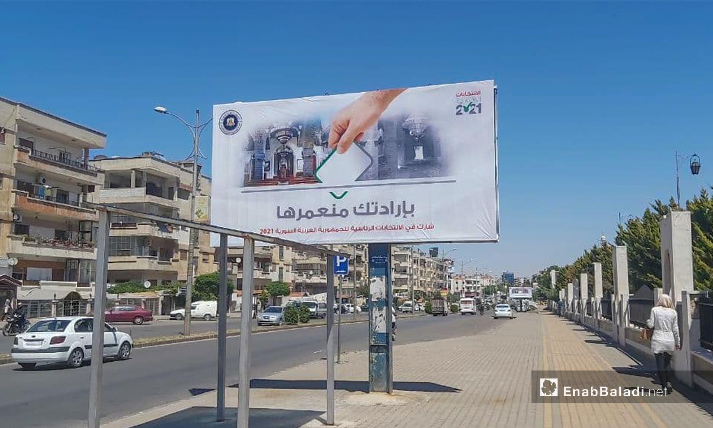 A billboard calling people to take part in the Syrian presidential elections - 12 May 2021 (Enab Baladi - Orwah al-Mundhir)