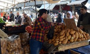 A greengrocer selling potatoes in Souq al-Hal Market  in Damascus (Athr Press)