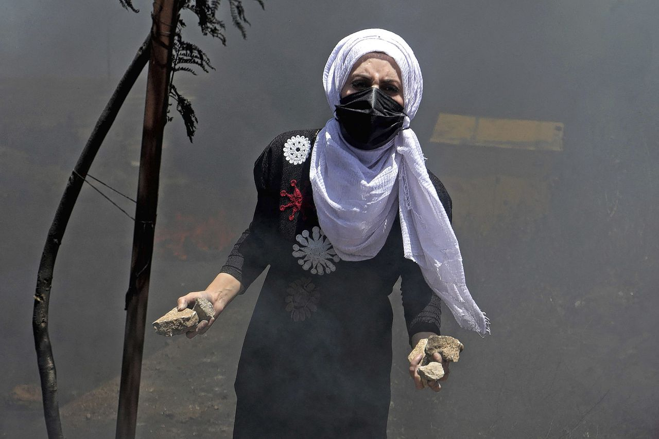 Palestinian protestor with stones in her hand amid heated clashes with the Israeli security forces near the Bet El settlement in the occupied West Bank – 18 May 2021 (AFP)