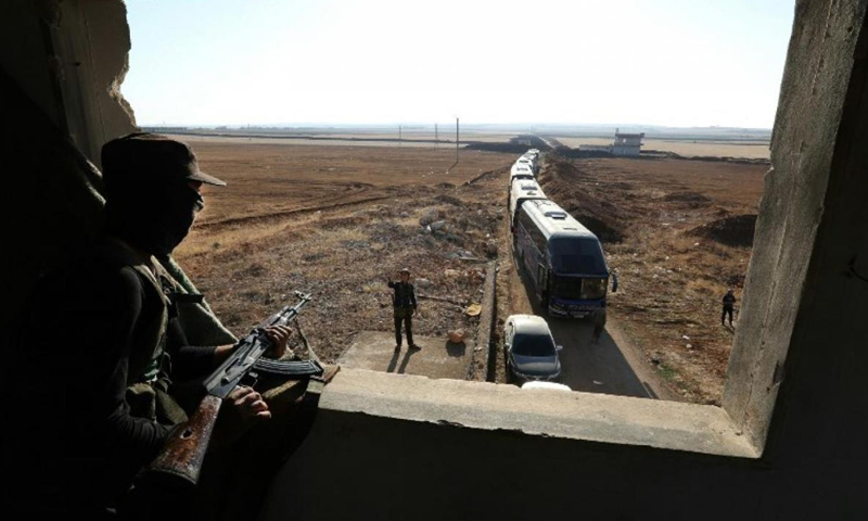 An opposition fighter looking at busses moving Kafriya and al-Fu'ah fighters - 19 July 2018 (Getty Images)