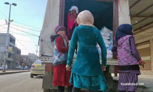 A group of young women unloading a sugar cargo from a truck in the al-Corniche Street in Qamishli city – 20 February 2021 (Enab Baladi/ Majd al-Salem)