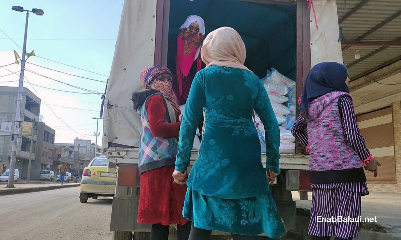 A group of young women unloading a sugar cargo from a truck in the al-Corniche Street in Qamishli city – 20 February 2021 (Enab Baladi/ Majd al-Salem)