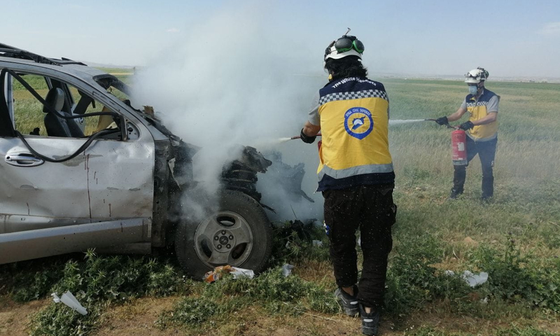Civil Defence members extinguishing a burning car that the regime targeted with a guided missile in the western Aleppo countryside - 6 May 2021 (Syria Civil Defence)