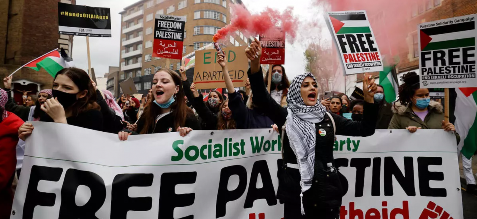 Activists and Palestine advocates holding Palestinian flags and smoke canisters in central London – 15 May 2021 (AFP).