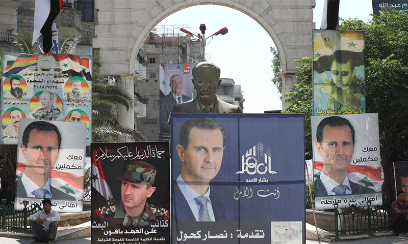 A man sits next to a statue of former Syrian President Hafez al-Assad, surrounded by election posters of his son, Syrian President Bashar al-Assad, in Damascus - 23 May 2021 (AFP)
