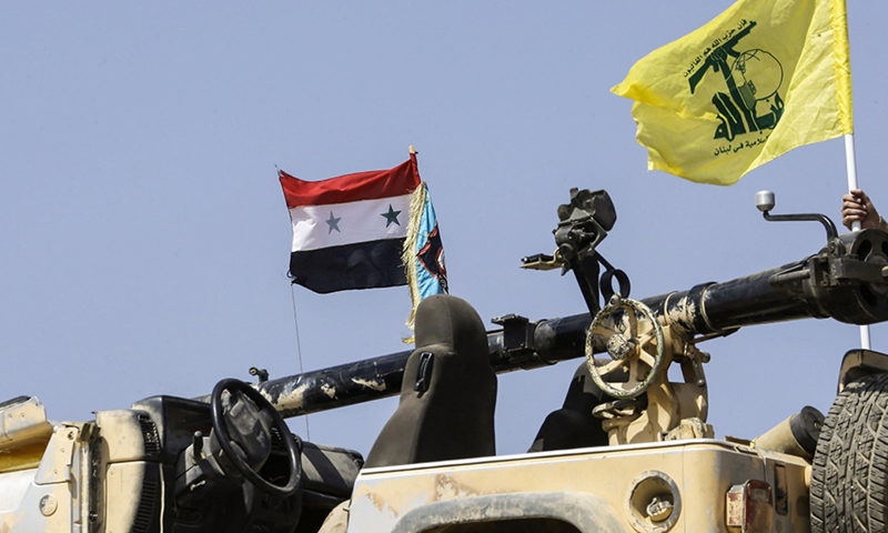 The Syrian flag held high along with Hezbollah's flag on top of a military vehicle on the Syrian-Lebanese borders - August 2017 (AFP)