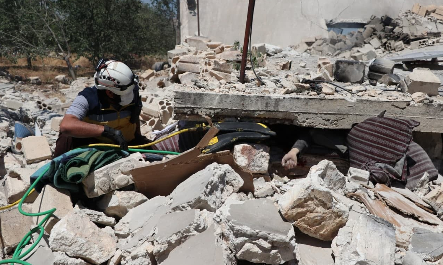 A Syrian Civil Defence member attempting to save a civilian from under the rubble of his home, south of Idlib - 6 June 2021 (Syrian Civil Defence)