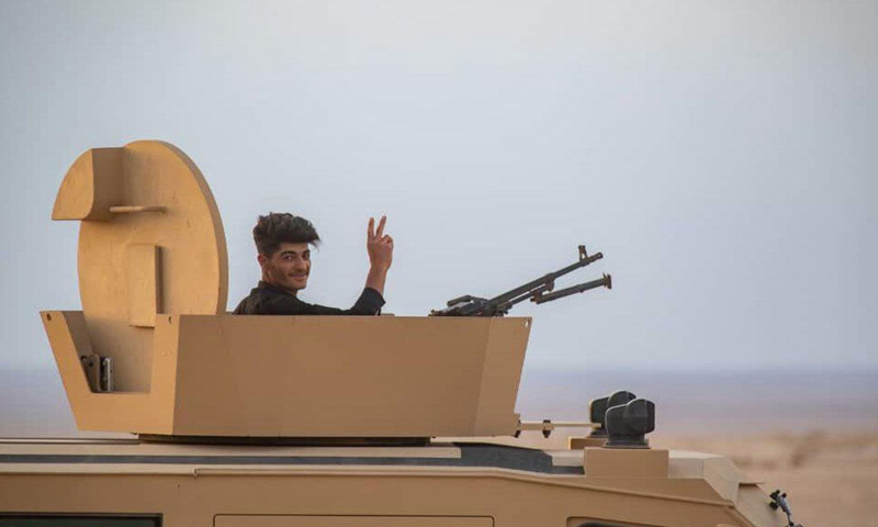 An SDF fighter raising victory sign while sitting on the top of a tank (Rudaw Media Network)