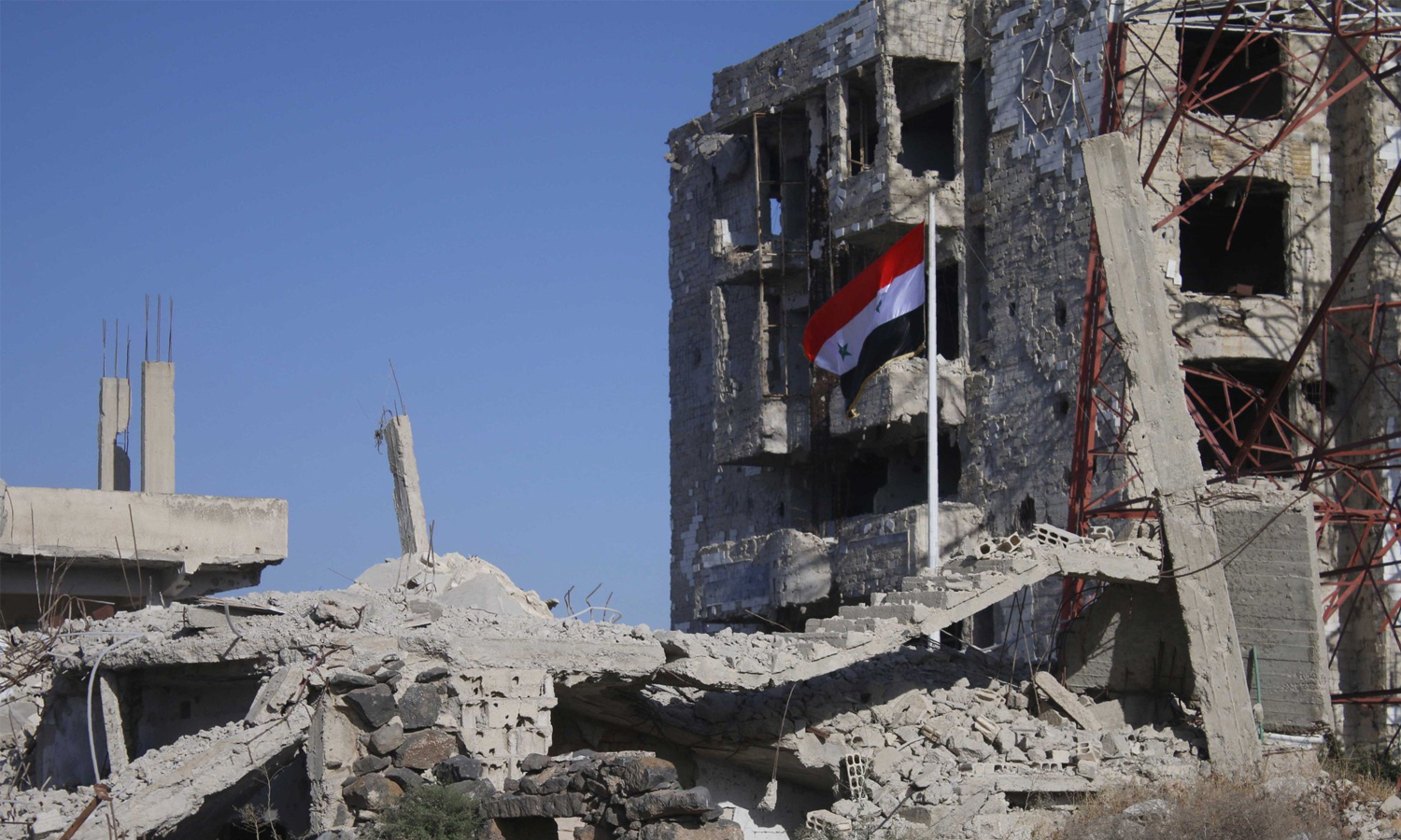 Syrian regime flag hoisted on the rubble of buildings in Daraa city — 12 July 2018 (AFB)