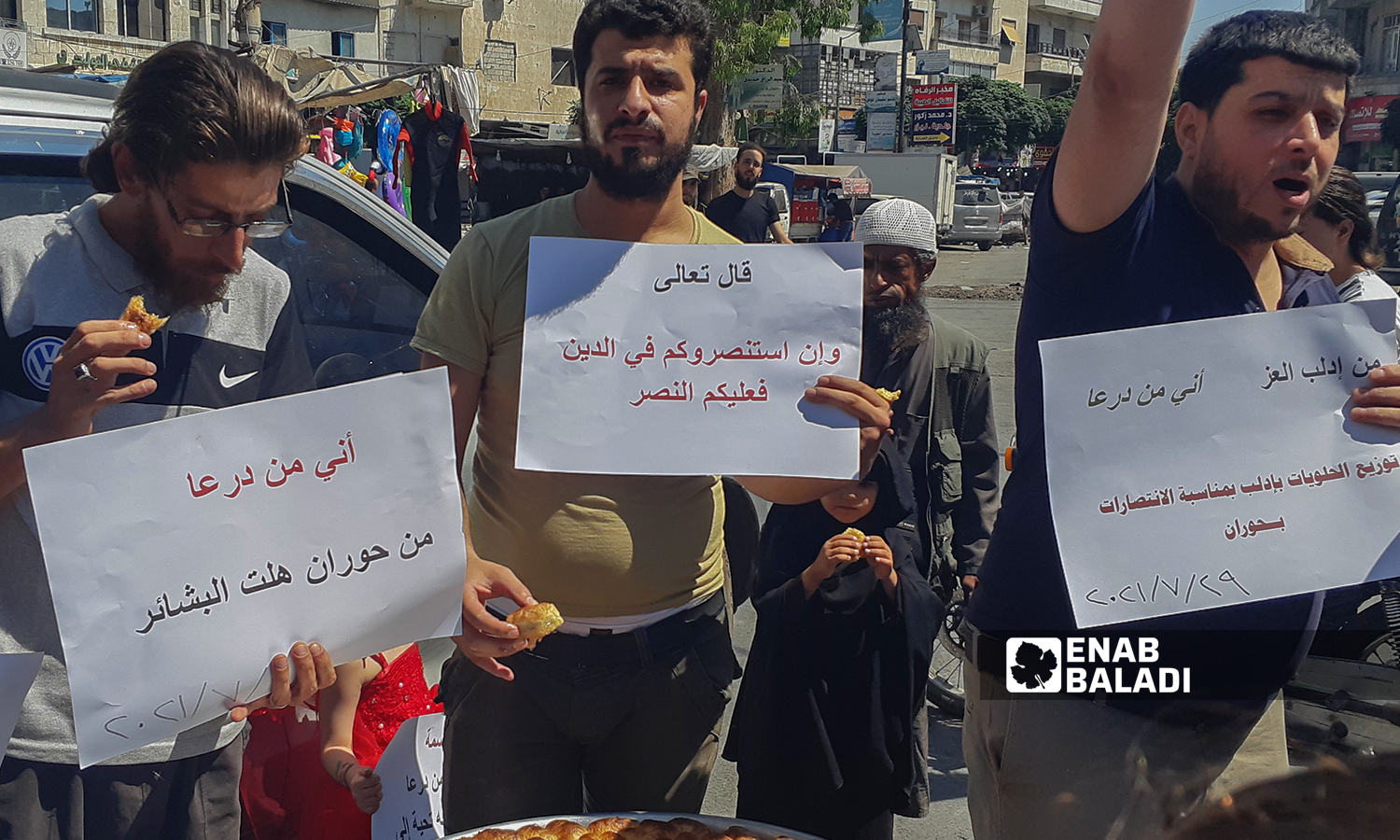 A group of young men carrying banners in solidarity with Daraa residents, and offering sweet desserts after the military checkpoints of the Syrian regime were erected - 29 July 2021 (Enab Baladi-Anas al-Khouli)