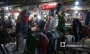 A child selling clothes at a stall in one of Aleppo's street markets - 4 July 2016 (Enab Baladi)