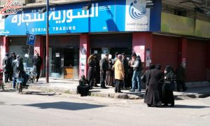 Citizens gather in front of one of the halls of the Syrian Trade Establishment in the city of Homs (Snack Syrian)