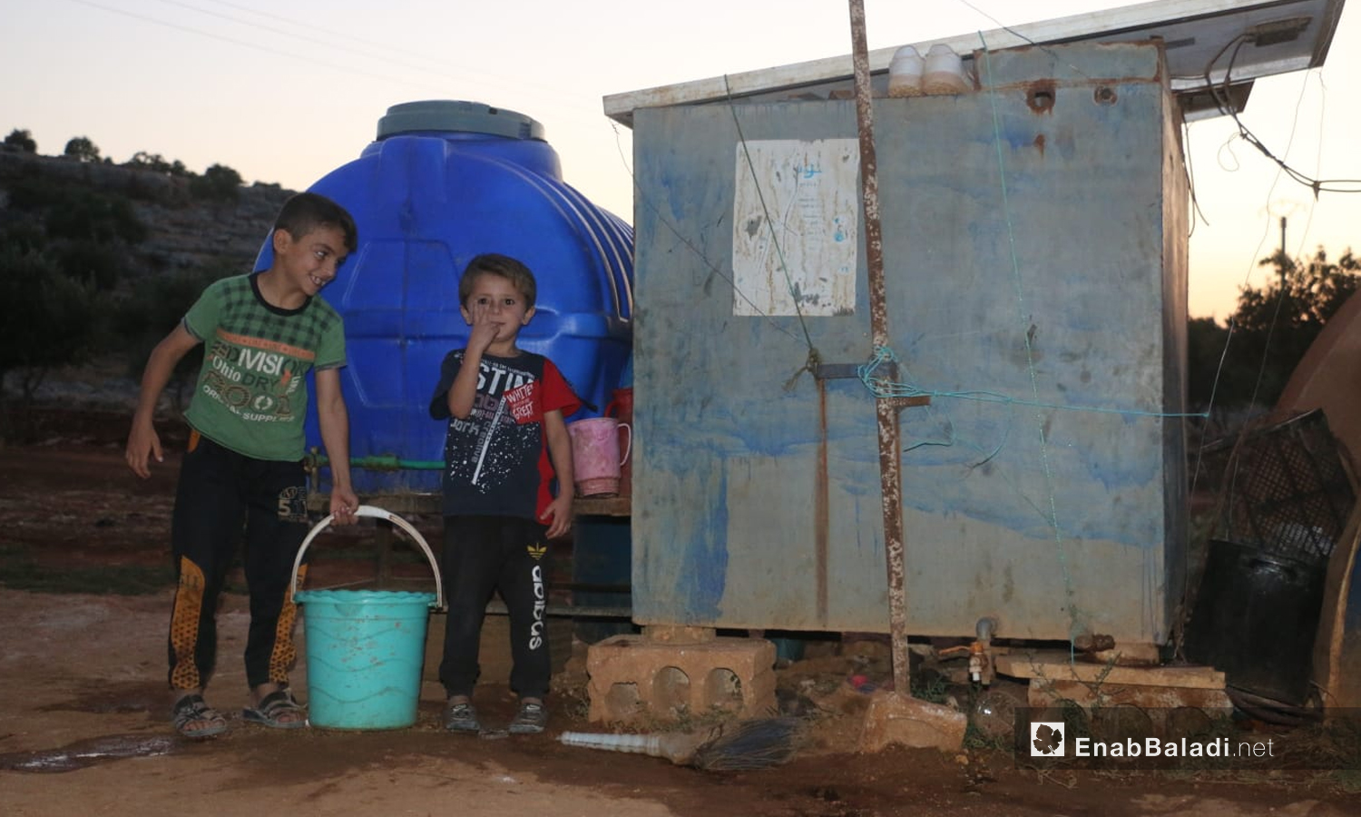 Syrian children near a water storage tank in a camp in the eastern countryside of Idlib- 21 June 2021 (Enab Baladi)