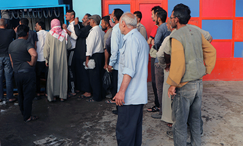 People standing in a queue at an ice blocks making factory amid power outages in al-Hasakah city - May 2021 (North Press Agency)