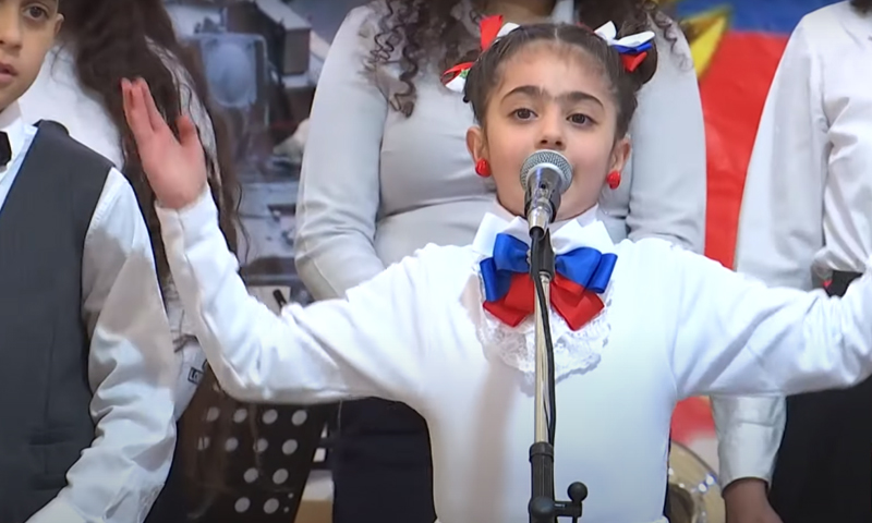 A Syrian child chanting a Russian song at Hmeimim airbase (RT)