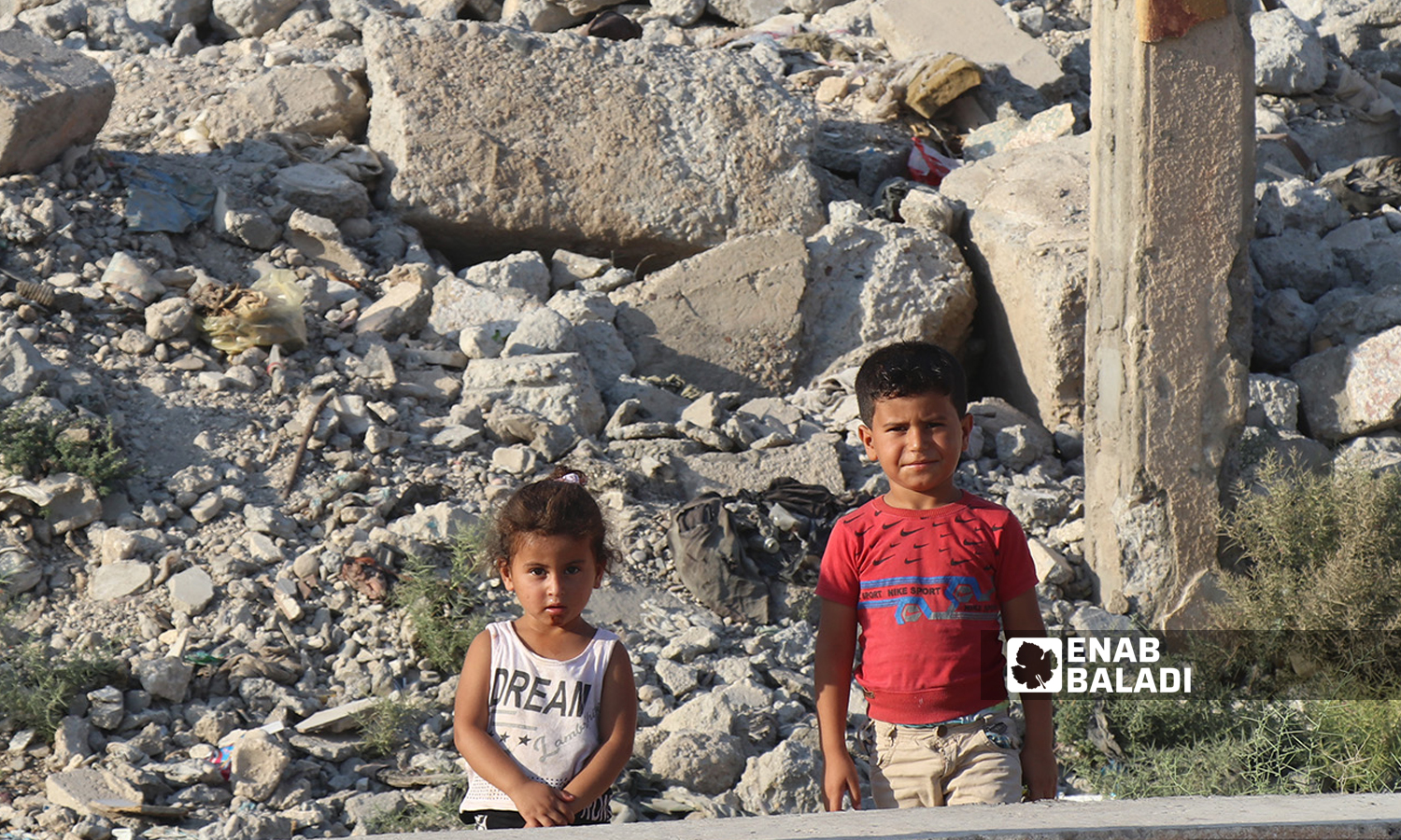 Two Syrian children standing in front of a destroyed building in Raqqa city in northeast Syria - 26 July 2020 (Enab Baladi / Abdul Aziz al-Saleh)