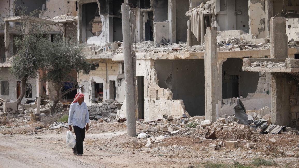 Syrian man passing near the rubble of buildings in a neighborhood controlled by the Syrian armed opposition in Daraa city, south of Syria — 2 October 2018 (AFP/Muhammad Abazaid)