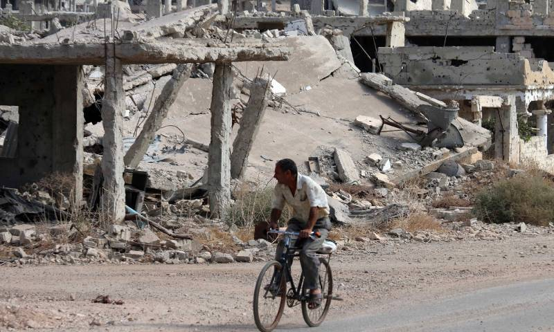 A Syrian man driving a bicycle near destroyed buildings in a neighborhood controlled by opposition factions in Daraa city, southern Syria - 2 October 2018 (AFP / Mohamad Abzed)