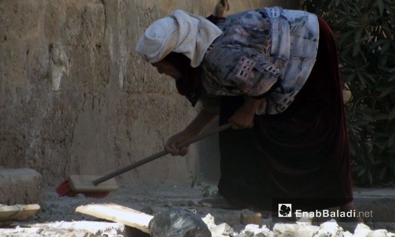 A woman sweeping the perimeter of her damaged house in Deir Ezzor - 2013 (Enab Baladi)