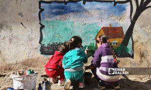 Syrian graffiti artist Aziz al-Asmar painting a mural of a house with the help of children on a wall in Binnish city in Idlib - 2019 (Enab Baladi)