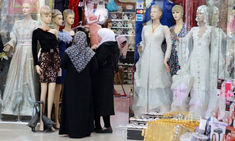 Syrian women looking at dresses displayed in front of a clothing shop in Souq al-Hamidiyah in Damascus old city - 3 December 2019 (AFP)