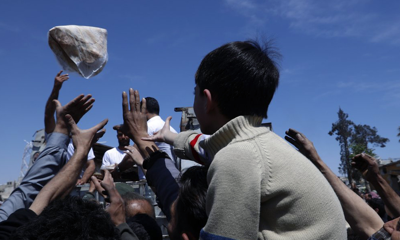 Syrian child struggling to obtain a bread bundle in Syrian regime-held areas (AP)