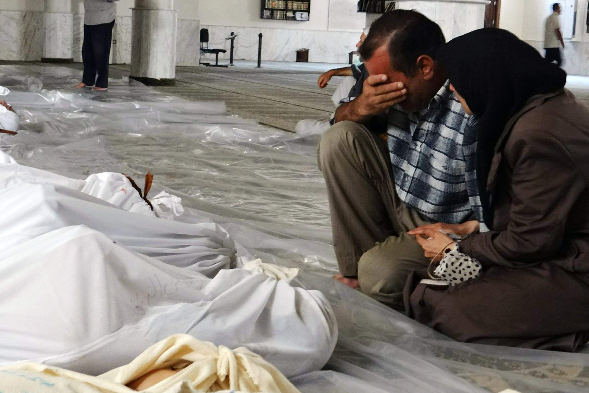 A Syrian couple crying next to the dead bodies of the people killed in the chemical attack on Eastern Ghouta, in Damascus's countryside — 21 August 2013 (AFP)