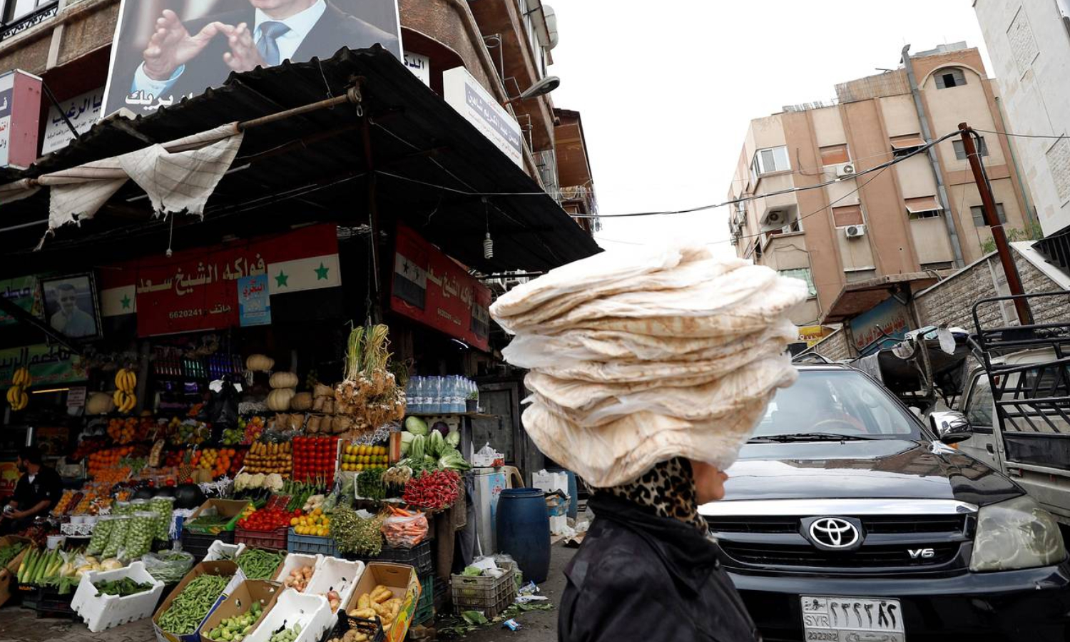 Syrian woman carrying bread bundles in Damascus city (Reuters)