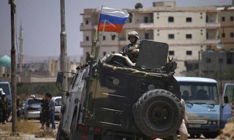 A Russian soldier standing inside an armored military vehicle watching anti-settlement local fighters being evicted from Daraa city - 15 July 2018 (AFP)