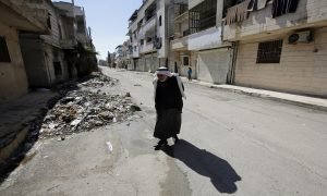 An elderly Syrian man walking in one of the residential neighborhoods of Homs city after the displacement of over 2000 civilians from the city following the siege lifting - 12 February 2015 (AFP)