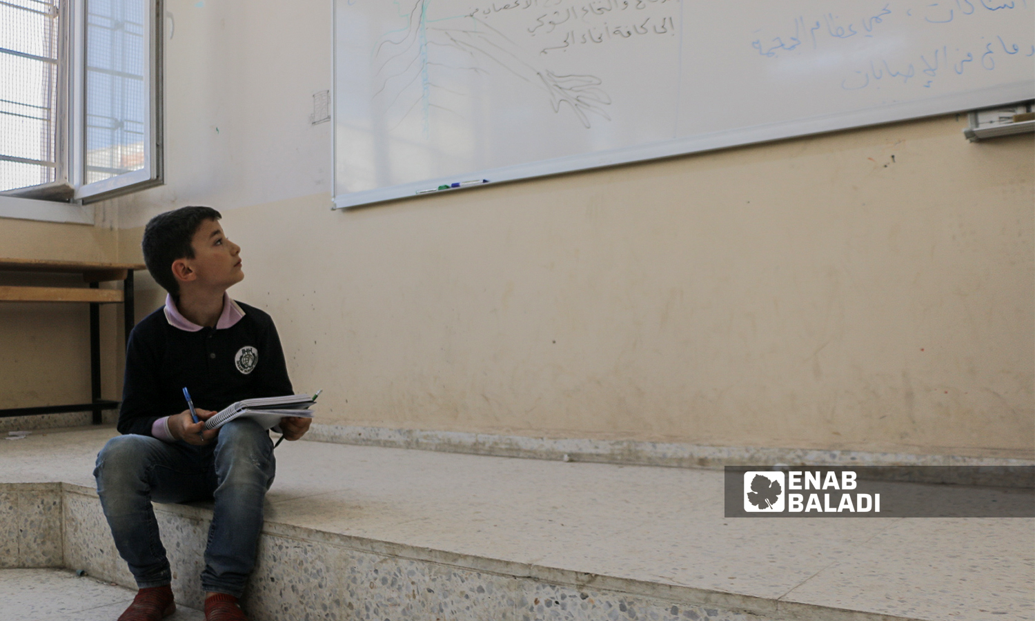 A primary schooler is sitting on the ground next to the whiteboard writing down his notes in a classroom in Azaz- 22 September 2021 (Enab Baladi- Walid Othman)