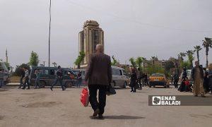 "An elderly Syrian man walking the street near the ""Municipal Palace"" tower in the al-Masharqa neighborhood in northern Aleppo - 17 April 2021 (Enab Baladi / Saber al-Halabi)"