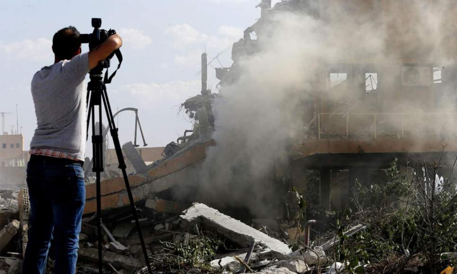 A journalist taking pictures of the Scientific Studies and Research Center (SSRC) for the production of chemical weapons in Barzeh near Damascus (Getty Images)
